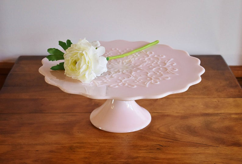 Blush pink milk glass cake stand standing on a wooden table with a white flower placed on top.