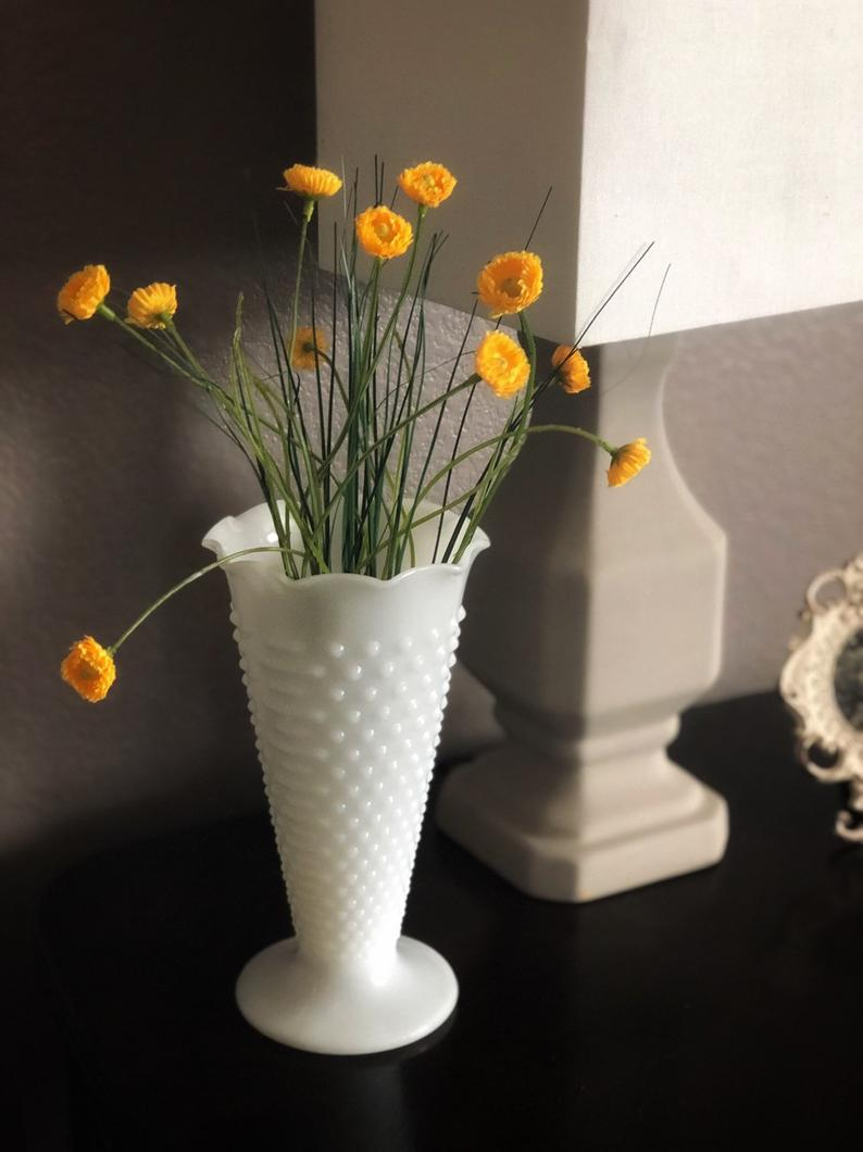 Vintage Hobnail Vase filled with flowers placed next to a lamp on a side table.