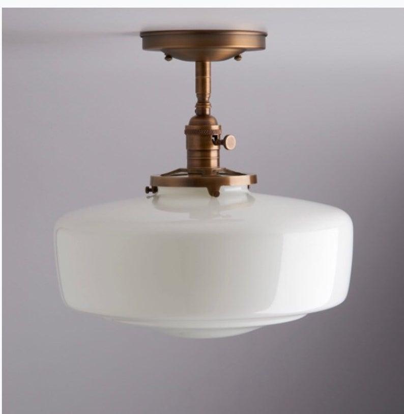 Flush mount milk glass light fixture with antique brass hardware.