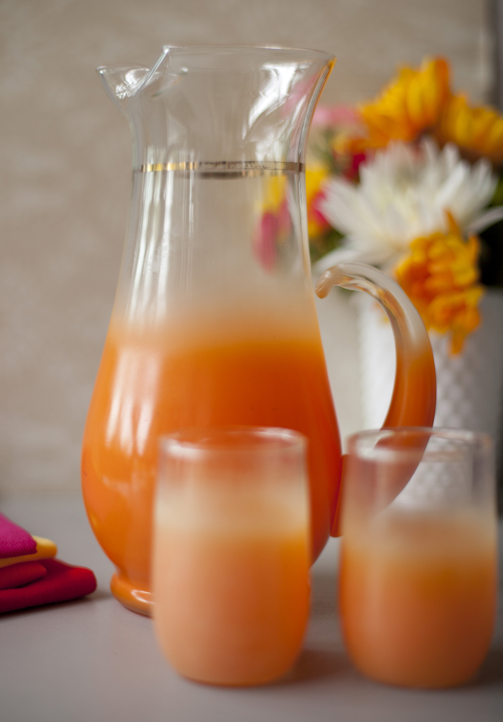 Bright orange Blendo Glassware pitcher and 2 tumblers placed near a vase of flowers.