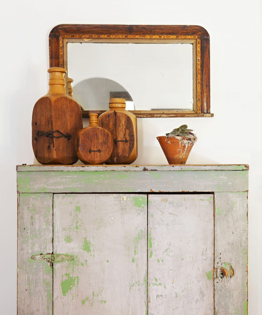 Vintage cabinet with antique pottery and mirror above it