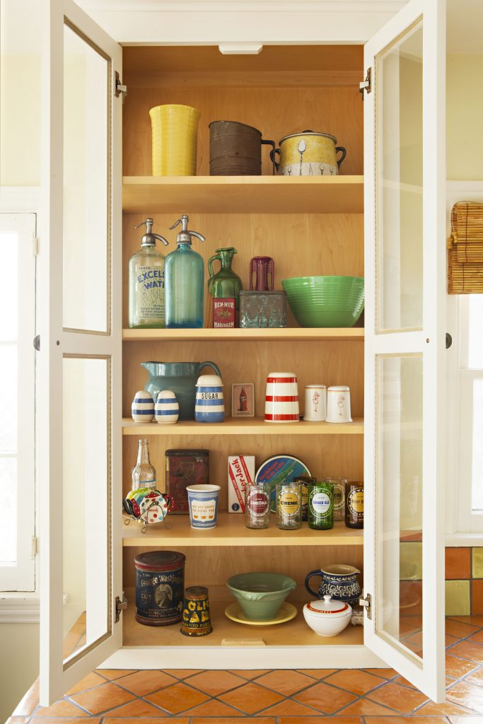 Open glass cabinets filled with antique pottery and dishes