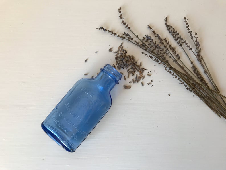 Hazel Atlas Blue Glass Medicine Bottle laid next to dried lavender stalks.