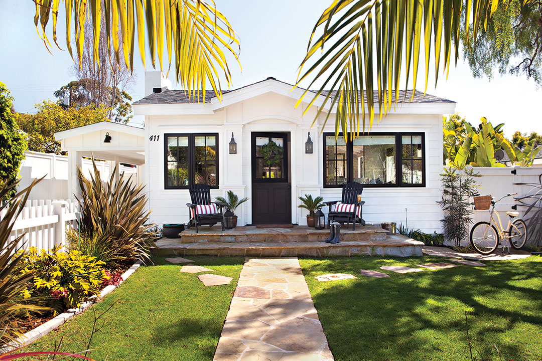 Patriotic cottage exterior with white paint and black trim.