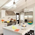 Cottage kitchen with white color palette, skylight and stainless steel appliances.