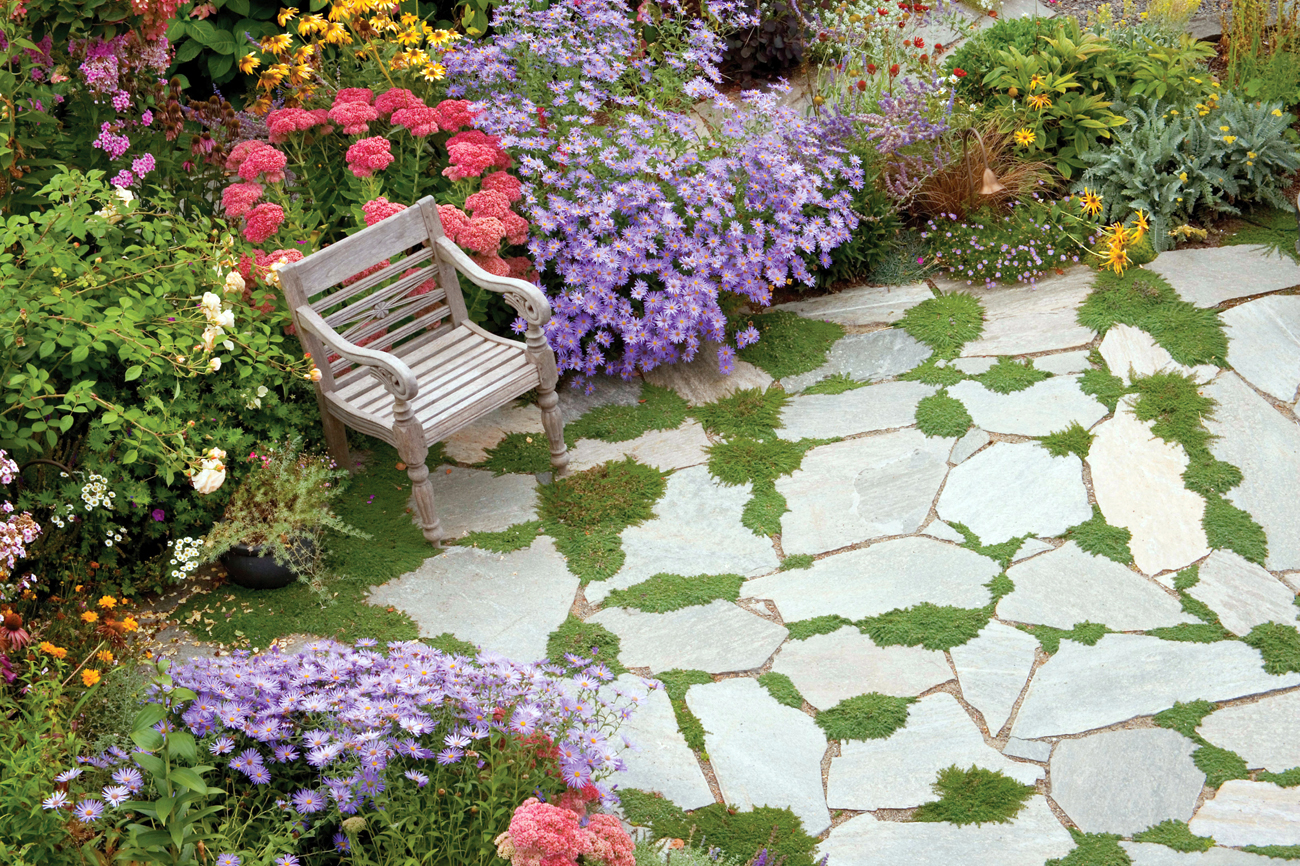 Cobbled stone path with moss growing around the cracks surrounded by pink, purple and yellow flowers and an ornate wooden chair.