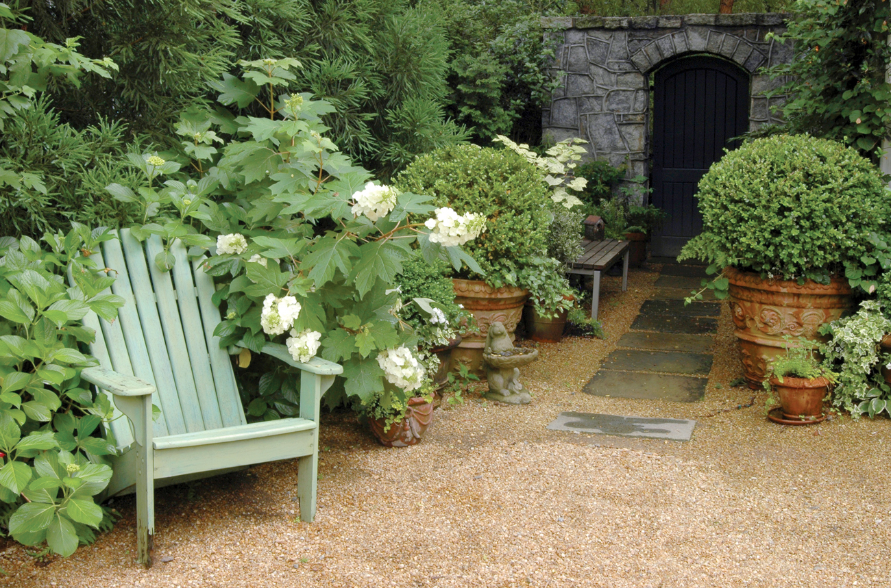A light green Adirondack chair surrounded by an overgrown garden near a path leading to a stone wall with a black door.