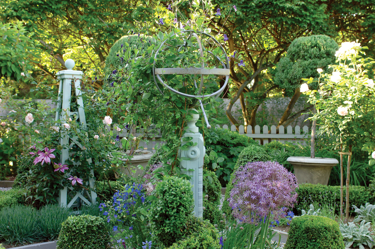Lush green yard with neutral colored picket fence in the background and metal sculptures artistically placed on the grounds.