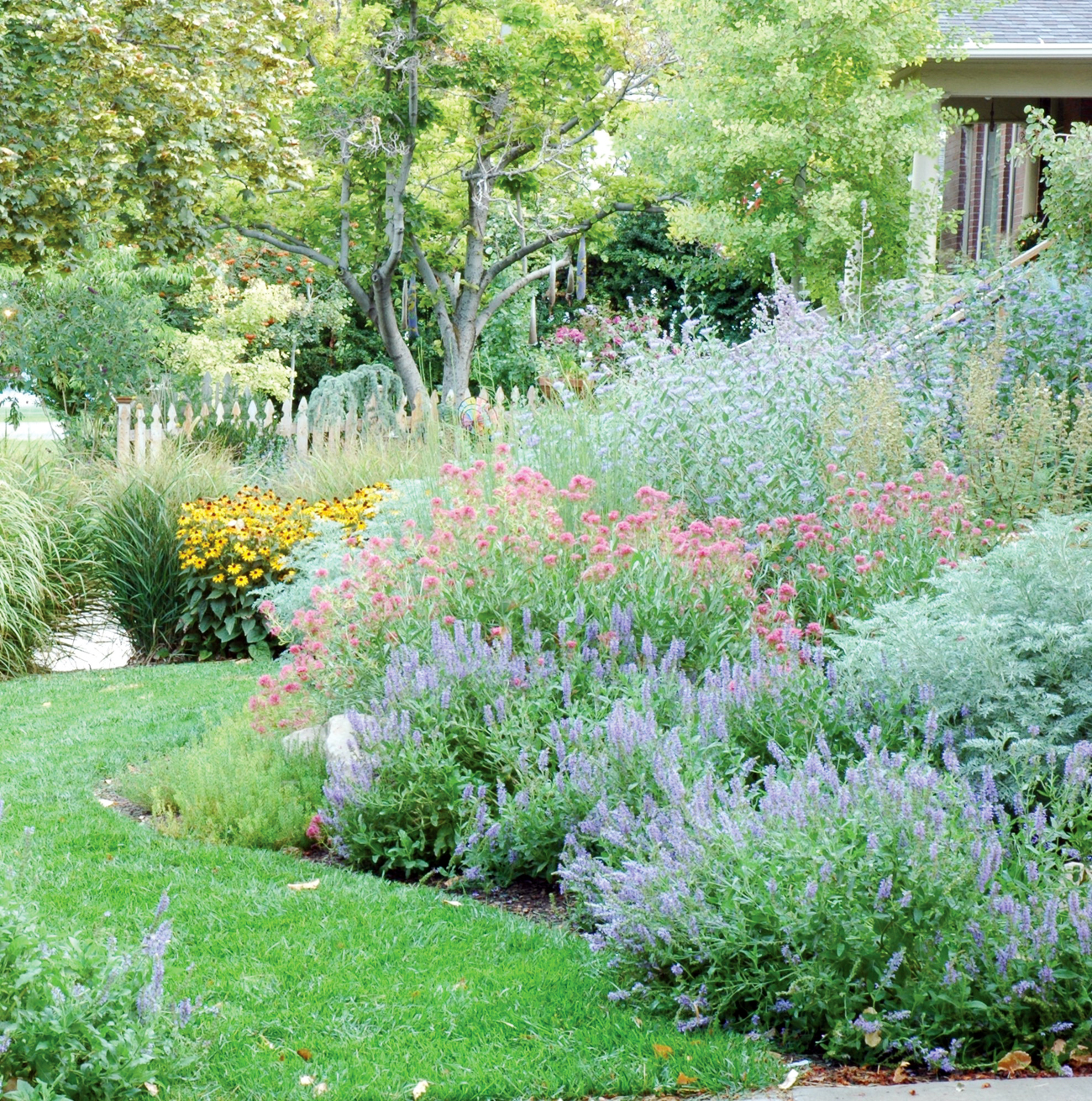 A lush lawn and a gorgeous hillside of vibrant varying colors of flowers.