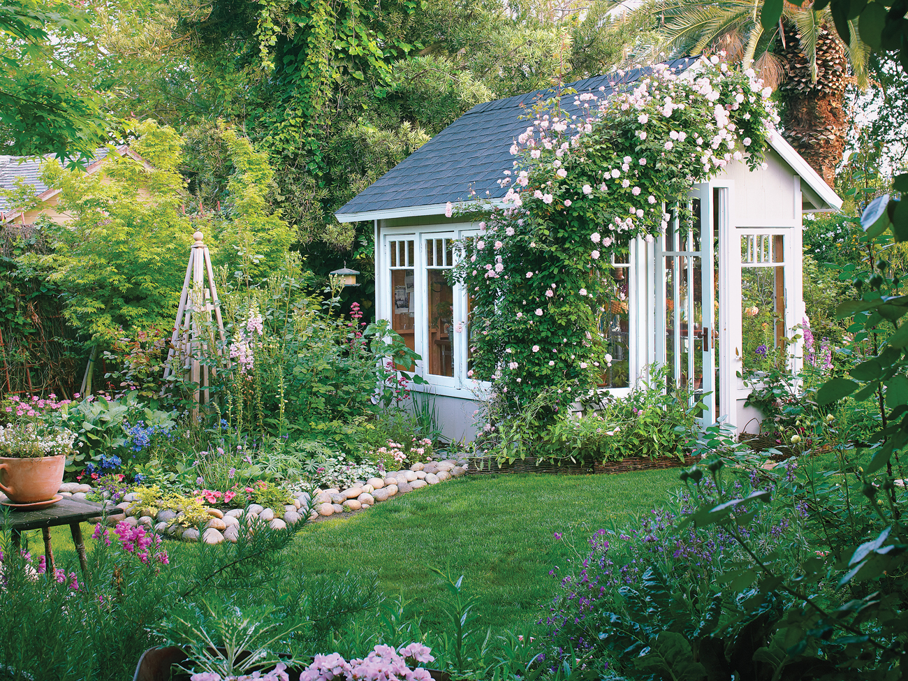 Vibrant green yard with a cottage style shed. The open shed door is welcoming and beautiful flowers grow up the side of the wall tying the shed into the yard.