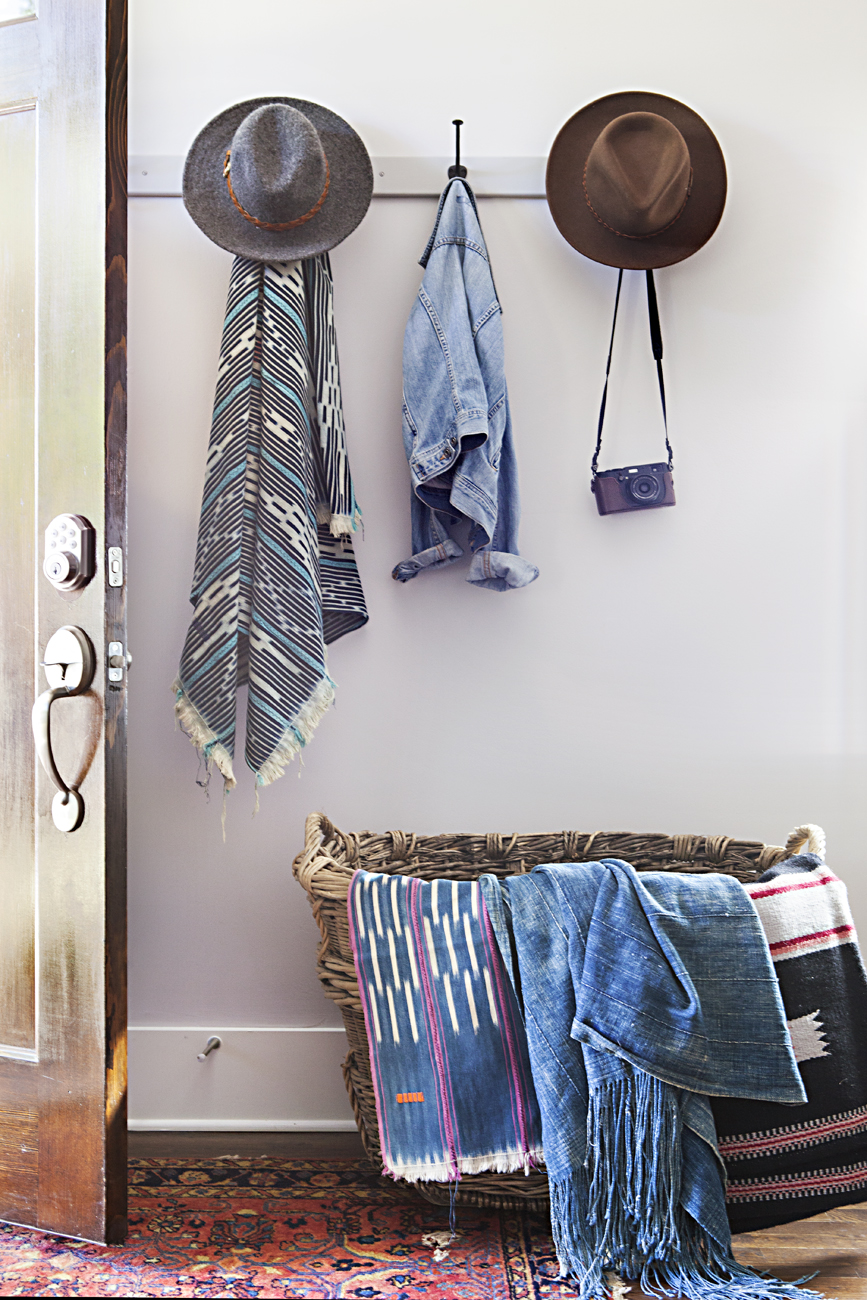 Textiles hanging over a woven basket and hats hanging on row of hooks behind the front door.