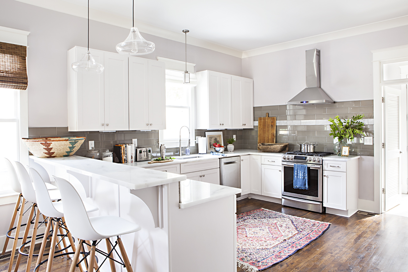 Bright, white open concept kitchen with vintage Persian rug.