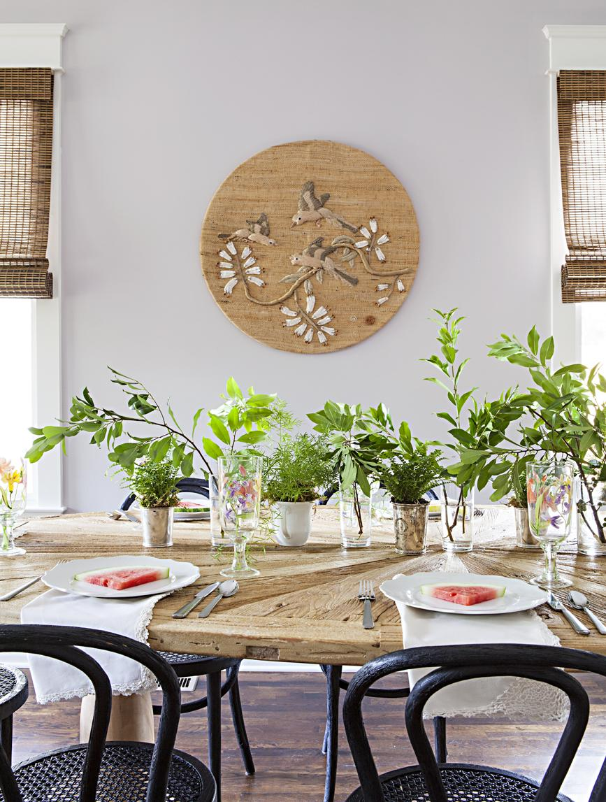 Rustic looking dining table topped with fresh greenery trimmings in vases.
