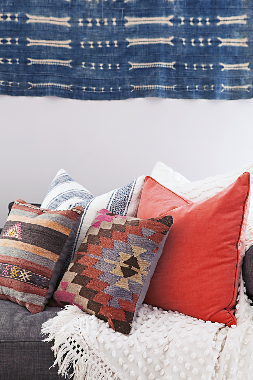 Vintage pillows arranged on a couch under a textile indigo mud cloth hanging.