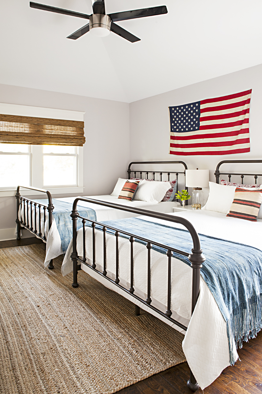 Americana guest bedroom with matching queen sized beds under a hanging American flag on the wall.