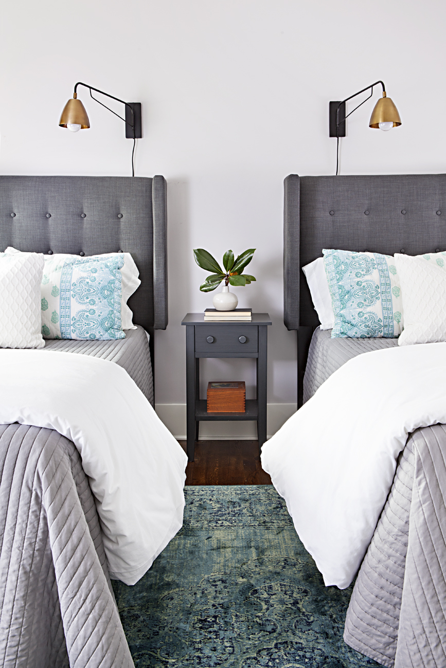 Guest bedroom with gray tufted headboard twin beds and vintage inspired blue rug.