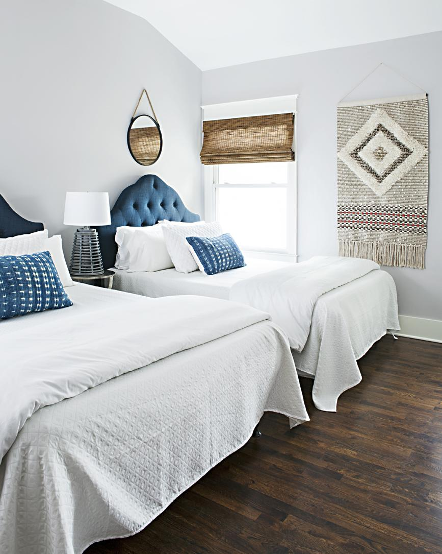Bright and open room with twi queen sized beds with tinted velvet blue headboards and hanging wall art.