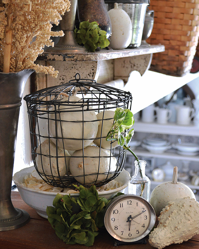 Wire cage filled with dried, cream colored pumpkins placed around a cottage as decor next to a shelf and an urn of dried flowers.
