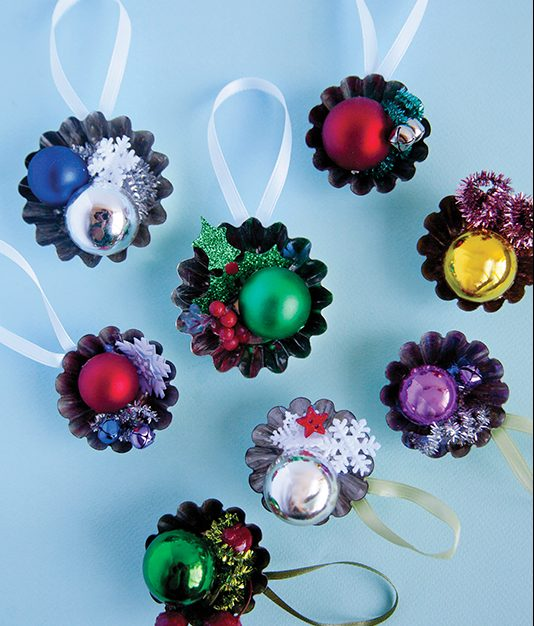 How To Do It: 1. Using a mini tart tin as the base, arrange the small decorative embellishments on top in your desired composition. 2. You can use a pencil to twist the pipe cleaners and formable garlands into a spiral shape.