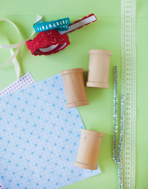 scrap paper. wooden craft spools and ribbon trim are ingredients for a DIY spool ornament