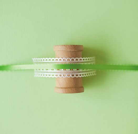 a layer of ribbon and trim are wrapped around a wooden spool to make an ornament