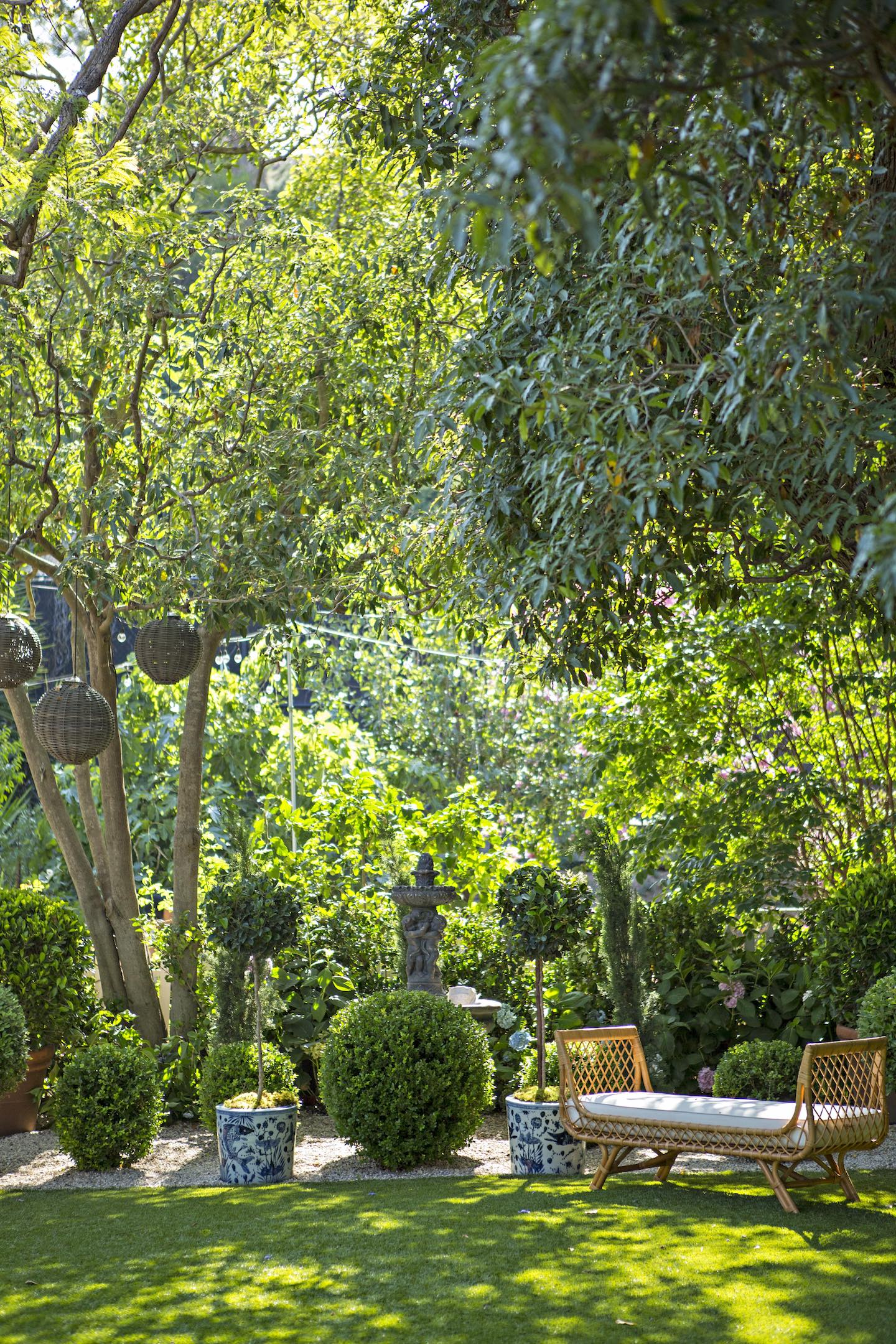 lush green garden with topiaries lanterns and a garden bench