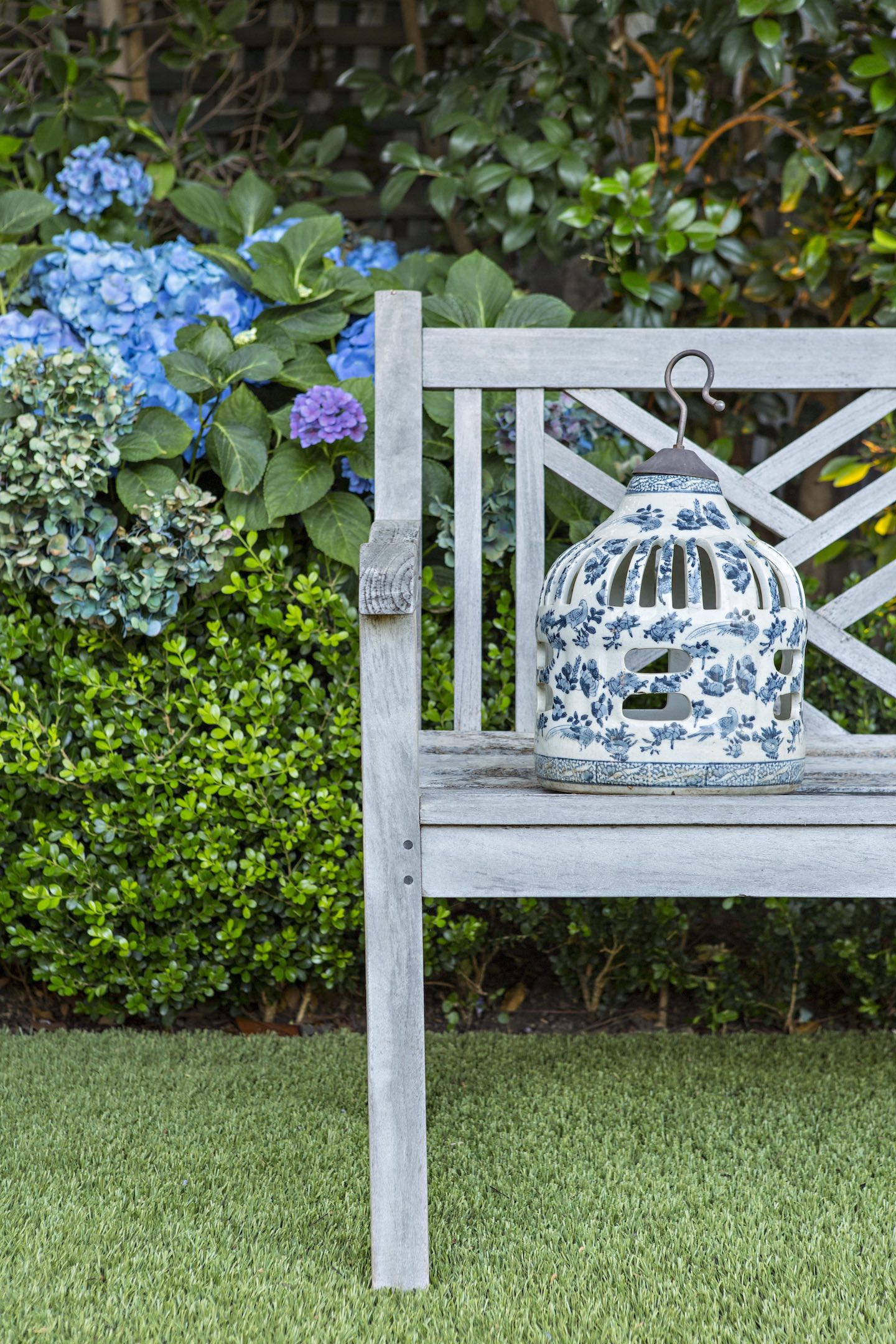 wooden garden bench with blue and white ceramic lantern