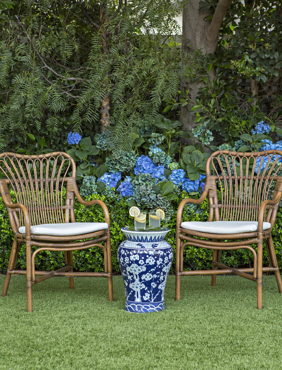 rattan chairs and a blue and white garden stool in front of hydragneas