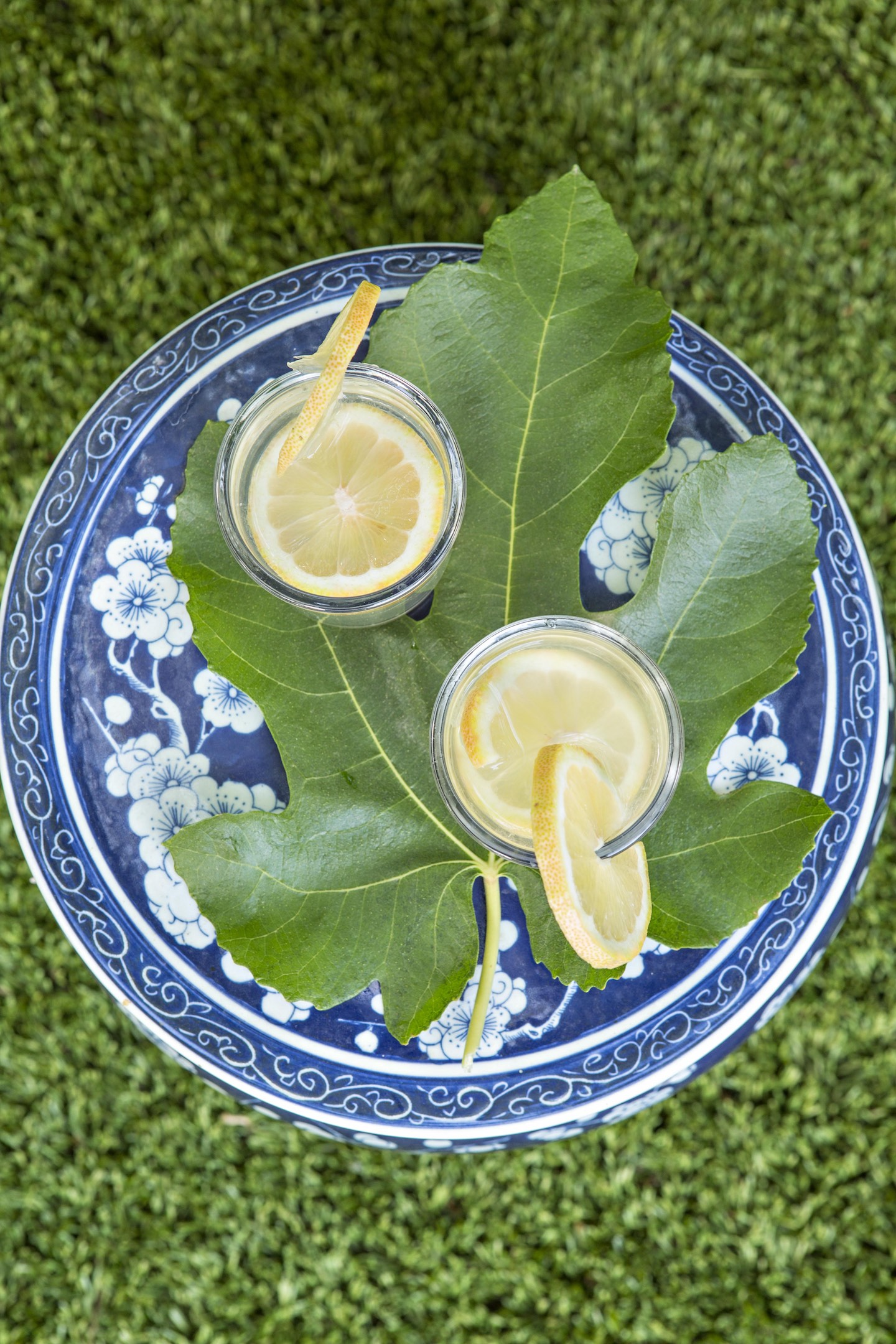 fresh lemonade on a big fig leaf and blue ceramic garden stool