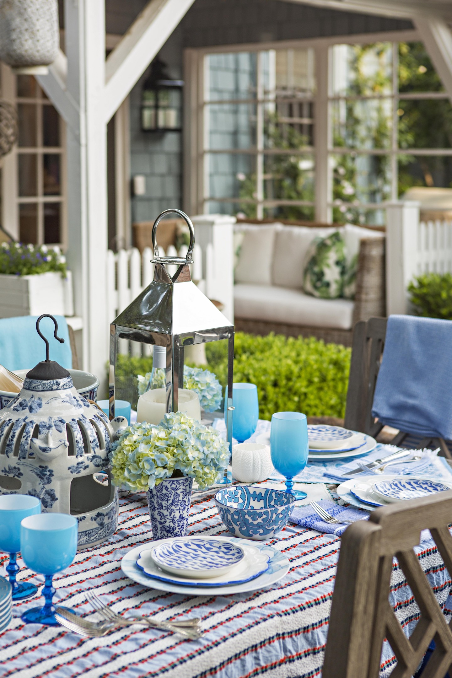 outdoor table set with striped tablecloth and blue glassware