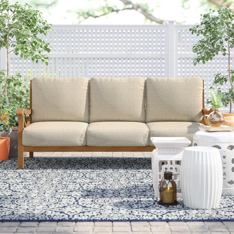 teak patio set on a white and blue garden patio
