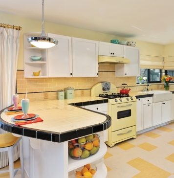 Retro kitchen with yellow tile and stove and black accents.