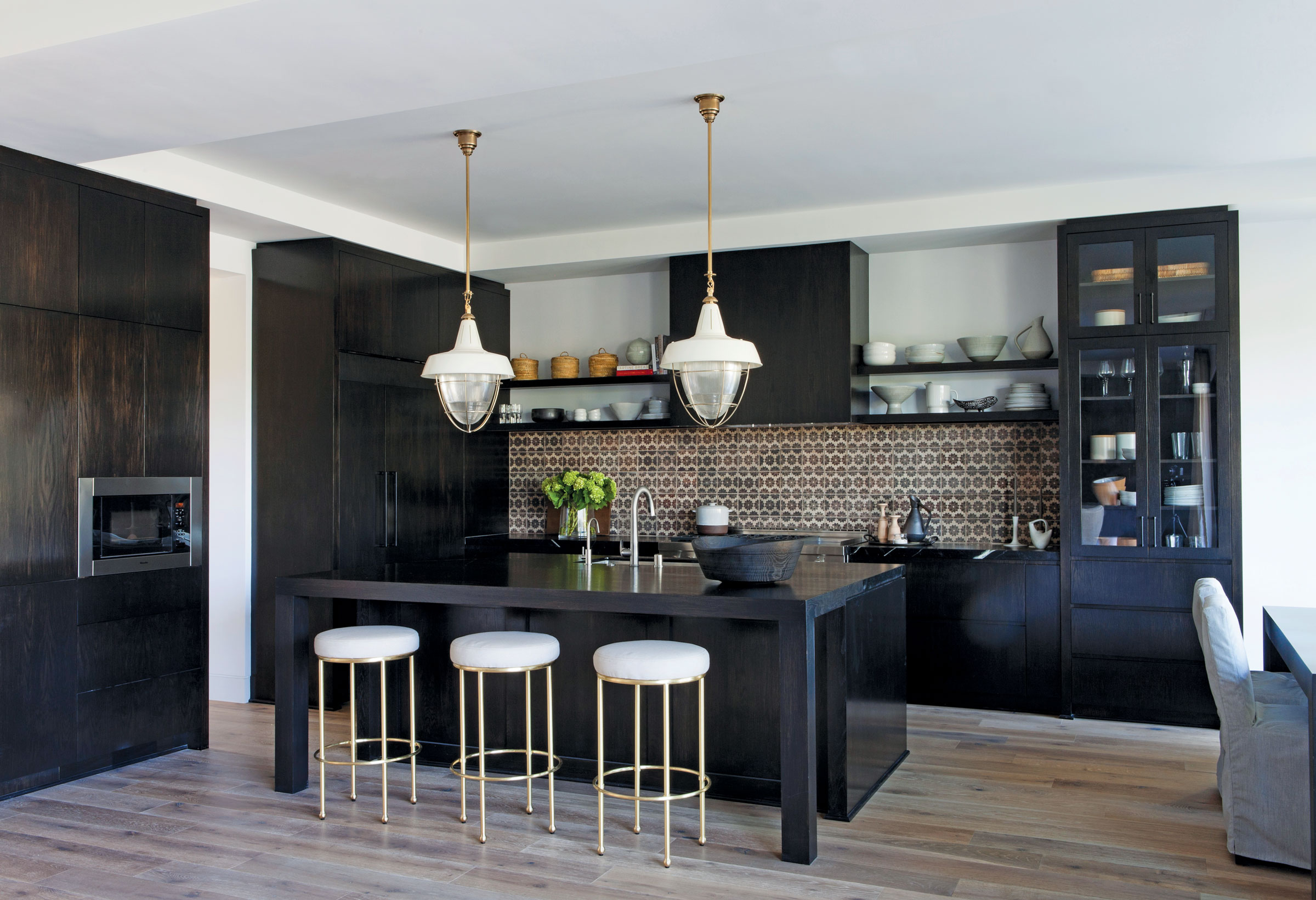 Black kitchen island with brown tile backsplash and overhead lights