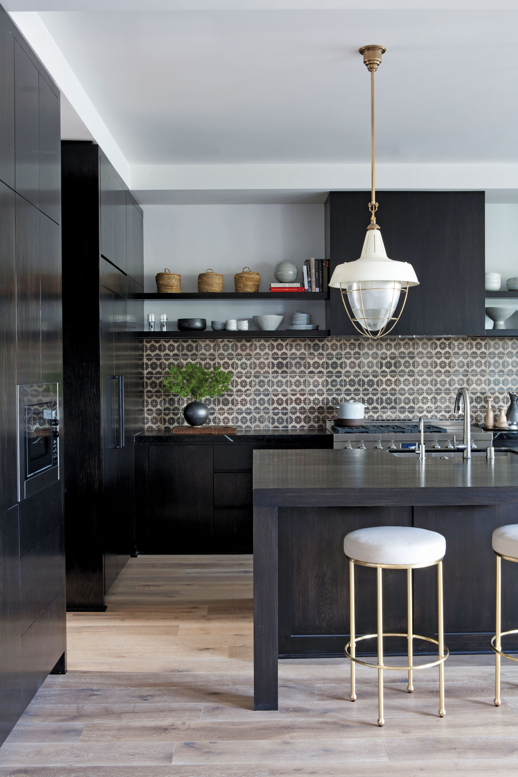 Light hardwood floors contrast black kitchen islands with tile backsplash