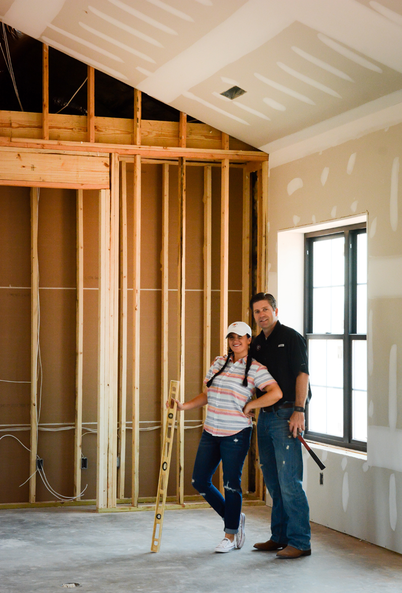 Katie and Ryan standing in the basic frame of their fixer upper farmhouse