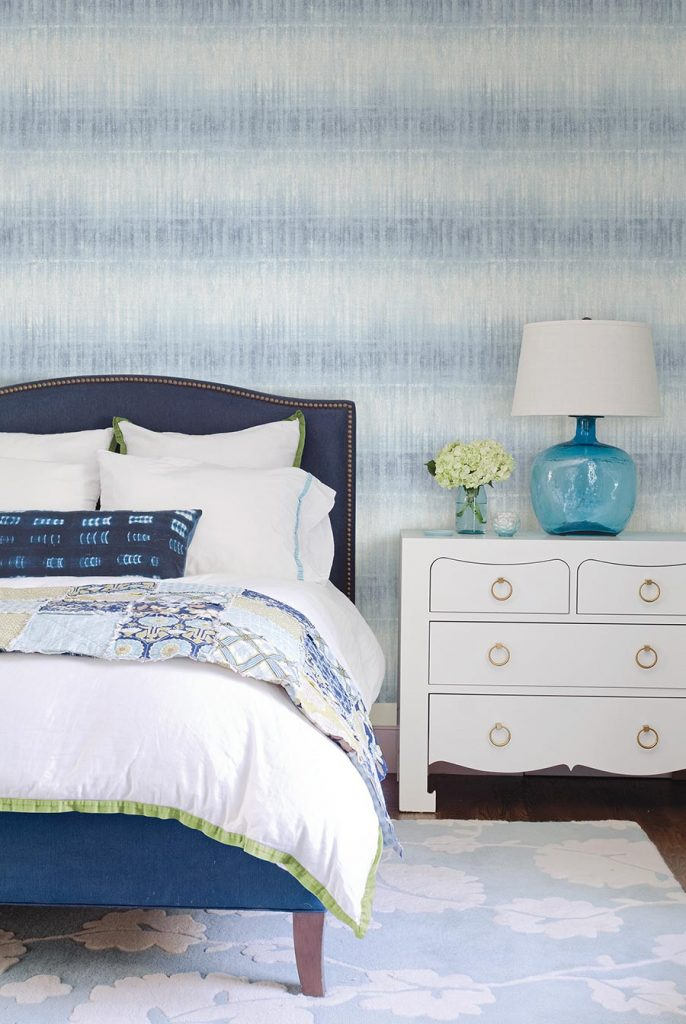 Pretty blue and white wallpaper which looks like a cross between ombre and ikat, gives a cool textural affect to this on-trend yet timeless bedroom.