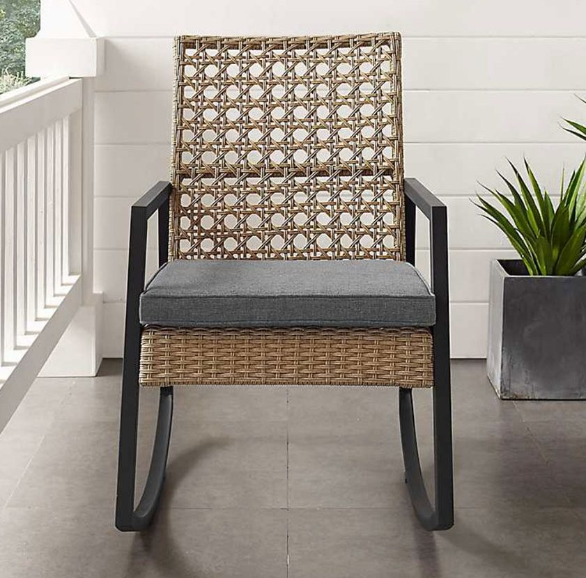 cane back outdoor rocker on a front cottage style porch which are summer bbq necessities for seating