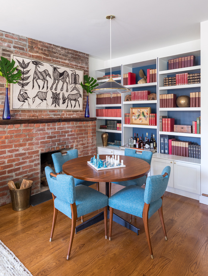 Dining room with brick and white accents and collected travel decor