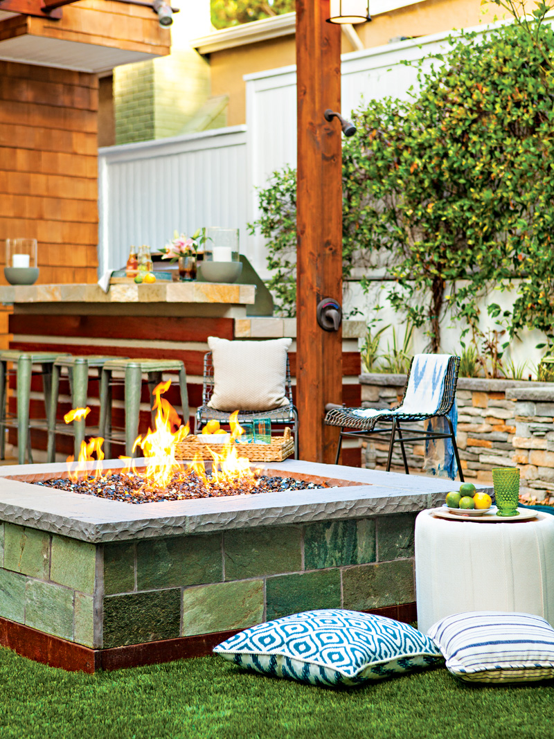 Built in fire pit surrounded by grass turf and a small seating area
