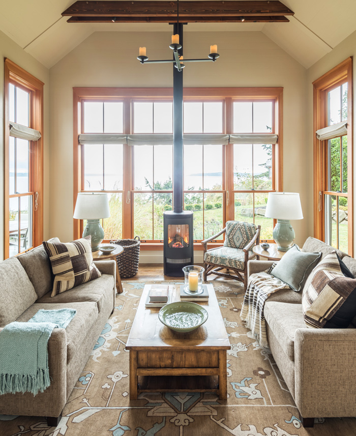 Open living room with large windows in Bainbridge Island cottage