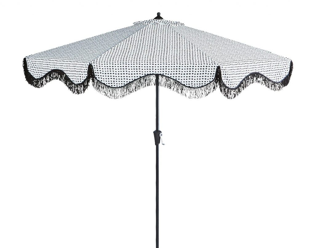 summer bbq necessities: patio umbrella with scalloped fringe trim. The pattern is white with small irregular black dots.