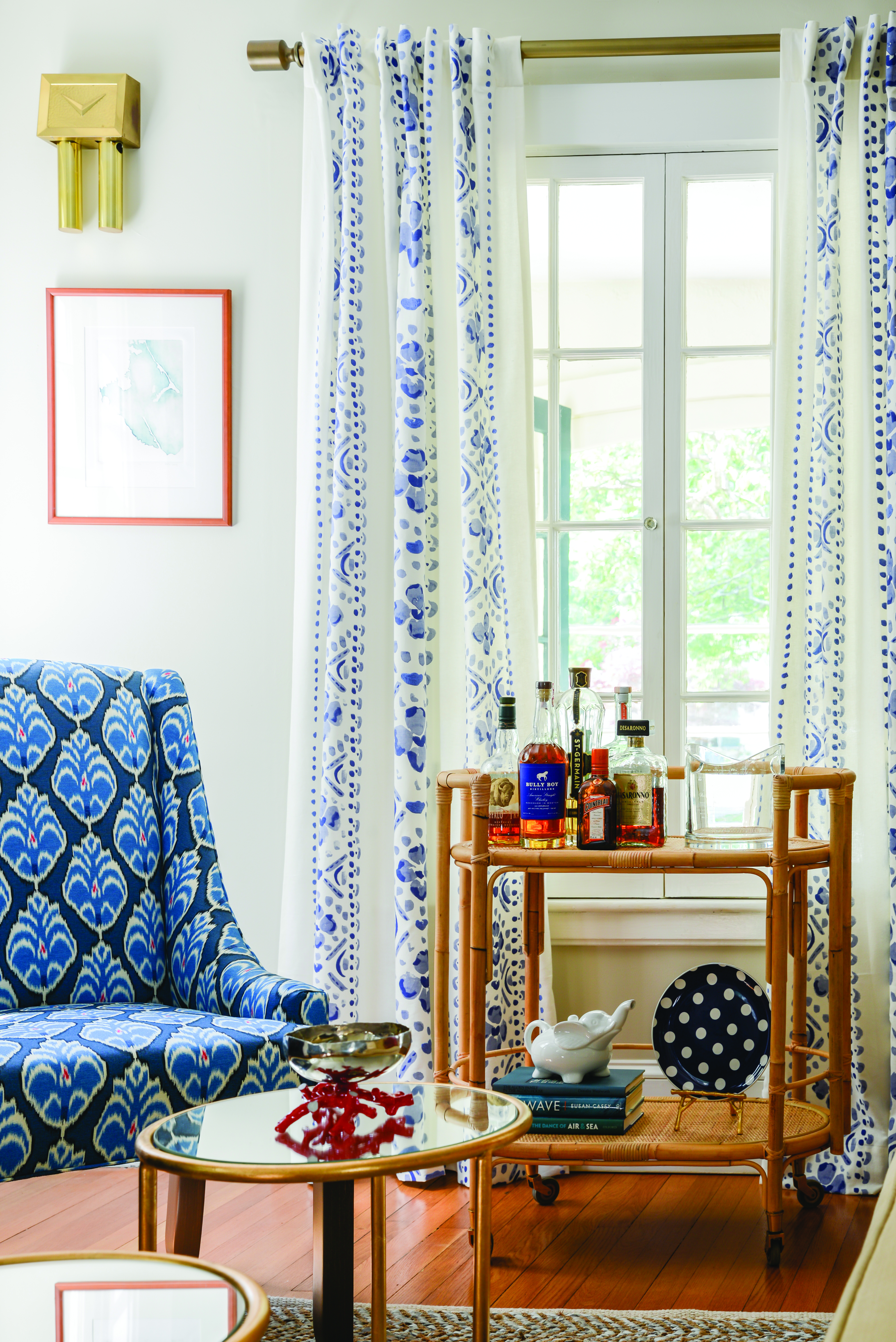 This blue patterned accent chair, shown here, and pops of color create a cohesive palette in this living room.