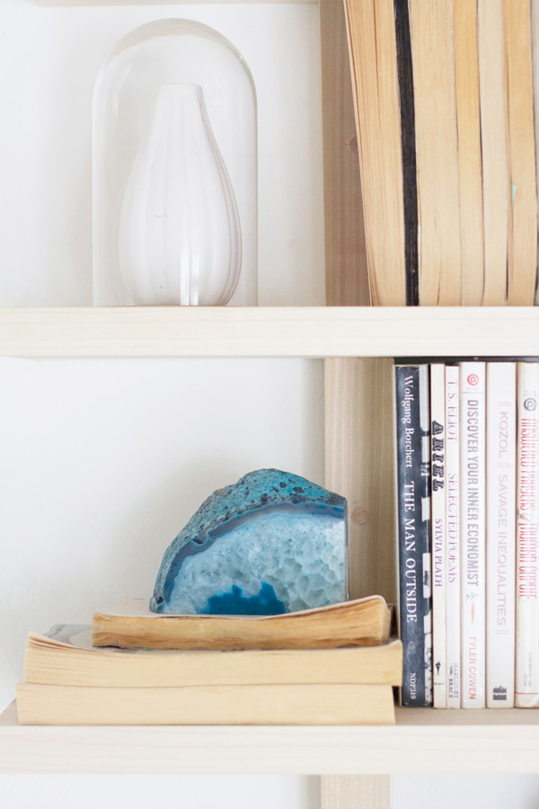 Books acting as décor is a functional and budget-friendly way to accent your home. A spectacular blue rock adds immediate earthiness to the shelf.