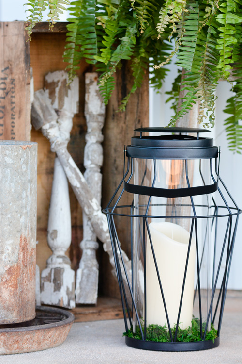 A mix of vibrant greens and vintage textures gives the porch a fresh, collected feel. The lantern sports a battery-powered candle with a timer—both from Balsam Hill—making it easy and fuss-free to entertain on the porch.