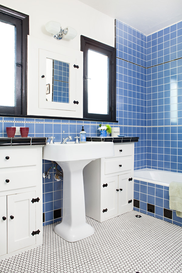 Restored Spanish bungalow bathroom with blue tile and black and white accents.