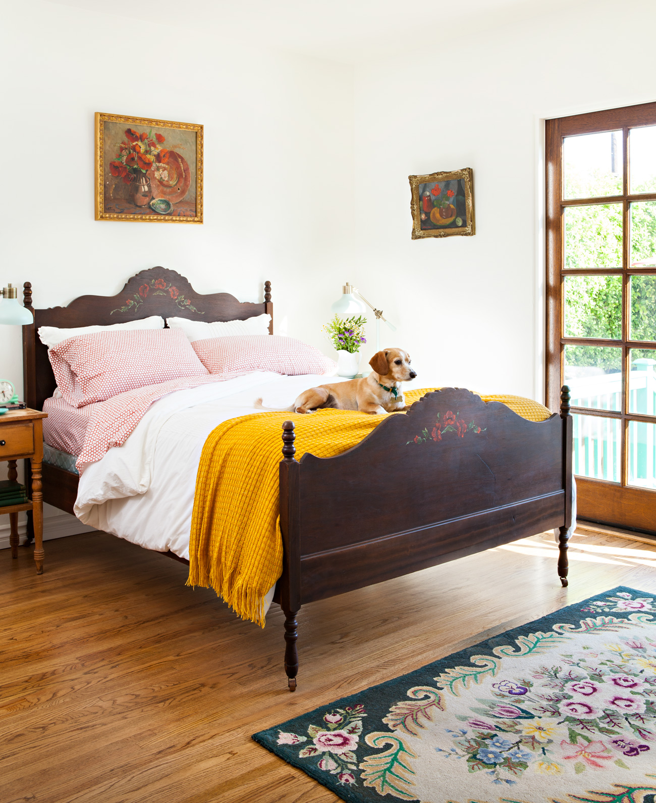 Antique bed in a spanish bungalow with vintage art on the walls and a yellow throw blanket on the end of the bed with a puppy on top.