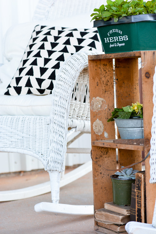 An old crate becomes the perfect stand-in for a plant stand adding Katie's signature vintage creativity to the porch.