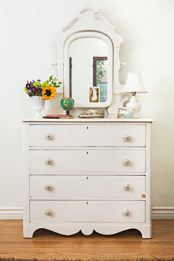 vintage dresser with chippy paint and an ornate attached mirror
