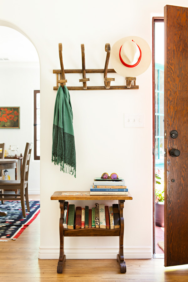 Spanish bungalow entryway with the wooden door cracked open and a small table and a hat rack.