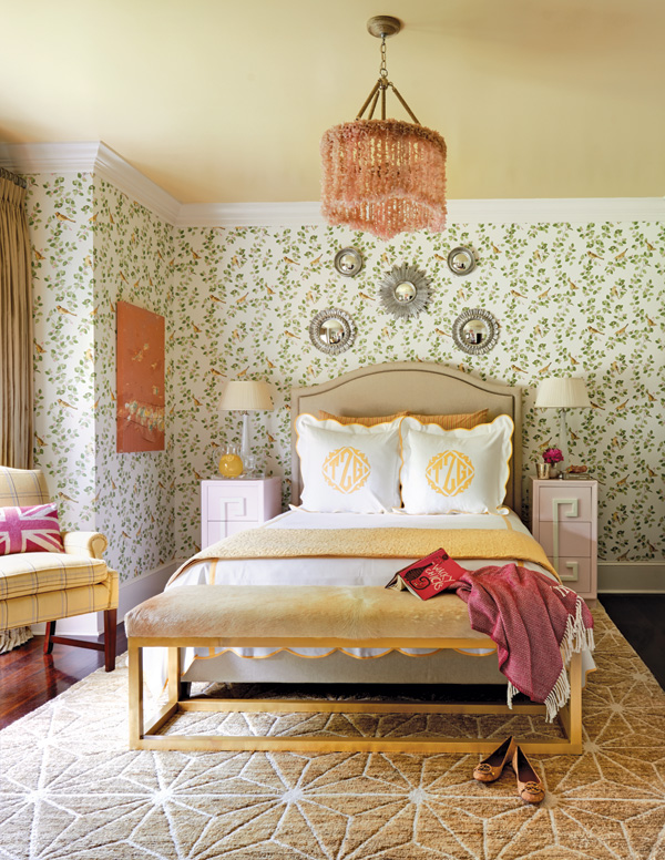 Full guest bedroom with patterned wallpaper and yellow décor accents.